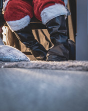 Low Angle View Of Santa's Feet Giving Away Presents To Children At Santa's Grotto During The Period Preceding Christmas.