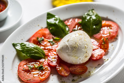 Caprese salad from mozzarella tomatoes basil olive oil an spices