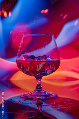 Glass of cognac with ice on a bright background