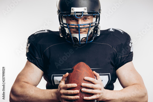 Muscular american football player in uniform and helmet holding ball, ready to play and fight for win, isolated over white background.
