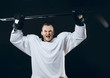 Hockey player wearing white uniform posing at camera with the hockey stick, celebrating the victory. Isolated on black background.