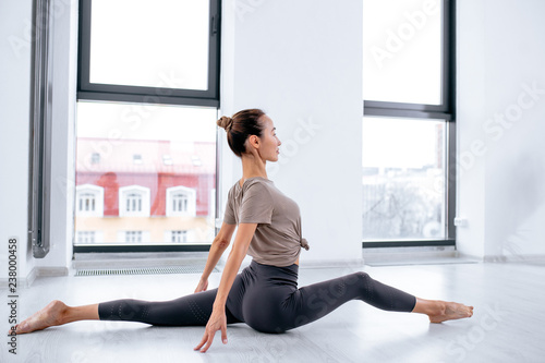 Montage in der Fensternische Yoga schule split on the floor. side view full length photo.young female athlete taking part in the competition