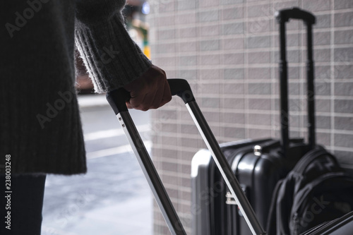 Fotografering  Closeup image of a woman holding and  dragging a black baggage for traveling