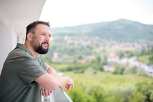 Man Standing On A Modern Balcony