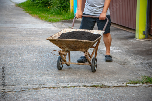 Photo  A man is pounding a clipper duo garden wheelbarrow.