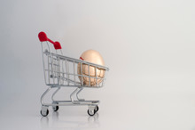 A Golden Egg Made Of Metal In A Supermarket Grocery Cart. The Concept Of A Unique Offer For The Client.