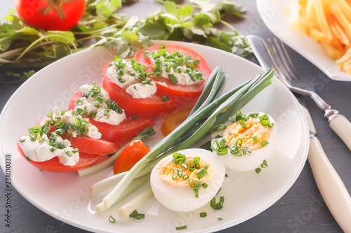 Fotografía  Half boiled eggs with tomatoes, green onions sprinkled with greens in a white plate on a gray wooden table