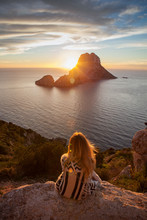 Woman Back To The Front Watching A Beautiful Sunset At The Beach. The Beach Is Called Es Vedra