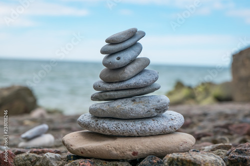 Photo sur Plexiglas Zen pierres a sable Pyramid of stones for meditation lying on sea coast at sunset