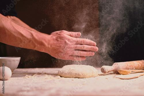 Deurstickers Bakkerij hands kneading dough on table