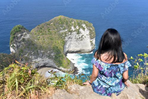 Fotografia  Tourist girl enjoying the beautiful landscape of Manta Bay or Kelingking Beach o