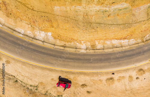 Fotografie, Obraz  Vertical aerial photograph of the cliffs and the road at the Dead Sea in Jordan, with a parked red car