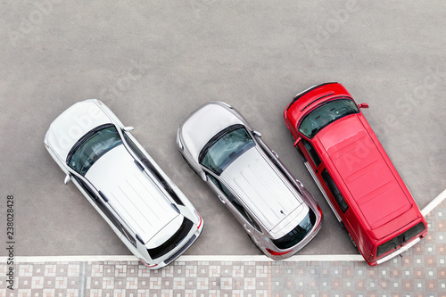 Car parked in aprking area at city street. Vehicles stand in row near road. View from above