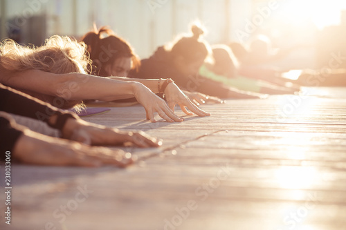 Staande foto School de yoga Child exercise, Balasana pose, working out. Yoga class. Group of sporty people doing yoga exercises in the morning at sunrise. Cropp shoot, sunny rays, healfy and calm concept, copy space