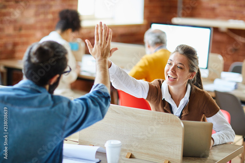 Cheerful and successful businesswoman giving high five to her colleague sitting in front of her
