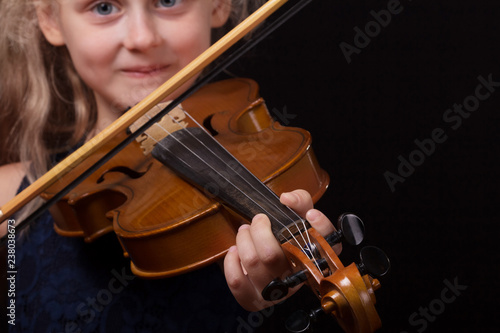 Happy little girl playing on violin on dark background - 238038673