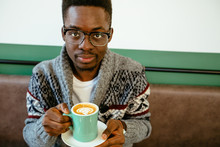 Handsome Pensive Afro American Man In Eyeglasses And Sweater Having Black Coffee Latte During Lunch, Sitting Alone At Cafe, Having Thoughtful Look, Looking At Camera. Warming In Snow Winter Day.