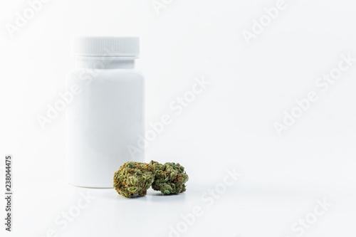 Fényképezés Medizinisches Cannabis neben einer weißen Tablettendose vor weißem Hintergrund