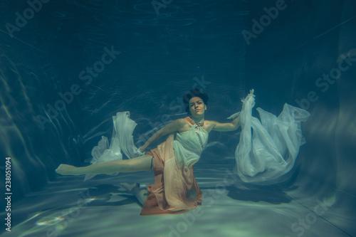 Fototapeta elegant slender girl swims underwater like a free diver in a white evening dress with beautiful fabric obraz na płótnie