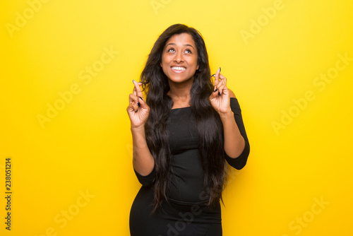Valokuva  Young afro american woman on vibrant yellow background with fingers crossing and