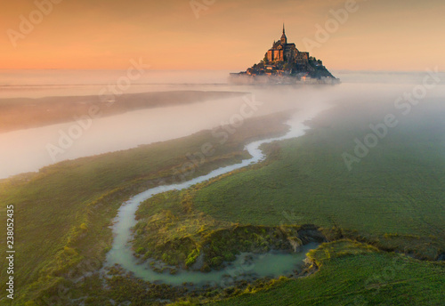 Foto aerial view to castle Mont Saint-Michel in orange sunset in France