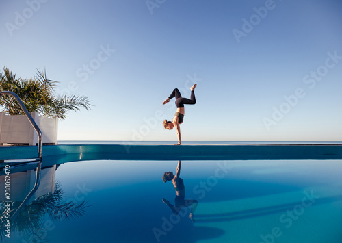 Fotografie, Obraz  Young attractive woman practicing yoga stand in Adho Mukha Vrksasana exercise, Downward facing Tree pose, working out by the pool, above the beach, relaxing against blue sky