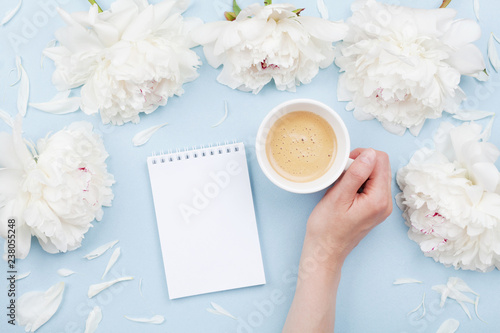 Woman hand with cup of coffee, open notebook and beautiful white peony flowers on pastel table top view. Cozy breakfast in flat lay style.
