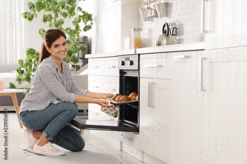 Beautiful young woman taking out tray of baked buns from oven in kitchen. Space for text