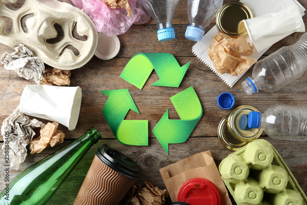 Fototapeta Recycling symbol and different garbage on wooden background, top view
