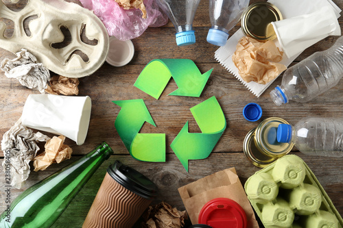 Recycling symbol and different garbage on wooden background, top view