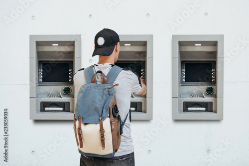 Obraz na plátne The tourist withdraws money from the ATM for further travel