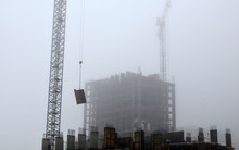 Construction Crane On A Construction Site In Conditions Of Cloudy Weather And Strong Mystical Fog