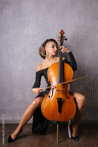 Cuadros en Lienzo Young woman in an evening dress playing the cello