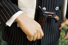 Male Mannequin's Hand With A Walking Stick On The Man Striped Suit Background
