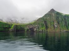 Steep Green Hornbjarg Cliffs And Waterfall, Biggest Bird Cliffs In Europe, West Fjords, Remote Nature Reserve Hornstrandir In Iceland, Misty Fog Ocean And Moody Sky