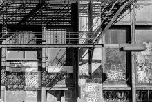 NYC Graffiti And Fire Escape On An Industrial Building With Dramatic Lighting