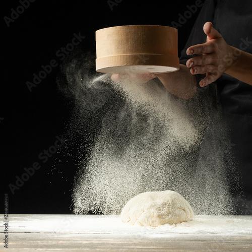 Fotografia A professional cook in a professional kitchen prepares flour dough to make bio-italian pasta