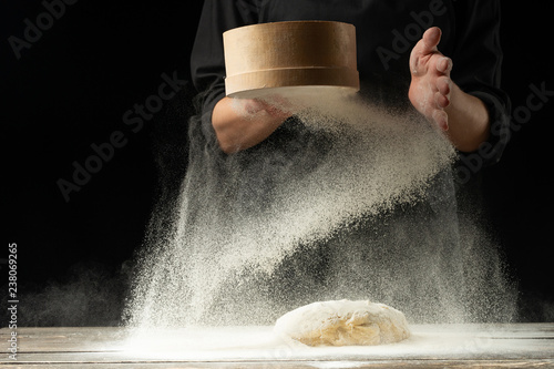 Fotografia A professional chef in a professional kitchen prepares dough from flour to cook Italian pasta, pizza, the concept of nature, Italy, diet and biology