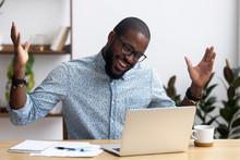 Joyful Black Businessman Sitti...