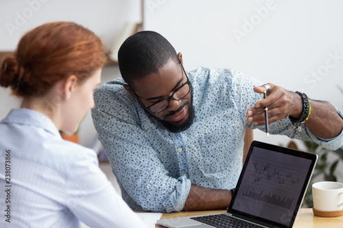 Fotografia Diverse millennial colleagues working together analyzing diagram looking at computer screen