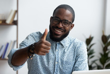 Head Shot Positive Confident Black Businessman Sitting At Office Desk Smiling Looking At Camera Showing Hand Gesture Thumbs Up Sign Symbol Of Good Result, Recommendation And Success In Work Or Study