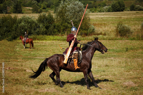 Fotografía  Equestrian soldiers in historical costumes is in the summer field