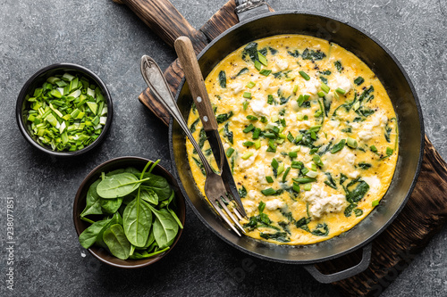 omelette with spinach and cheese in a pan on the concrete background top view