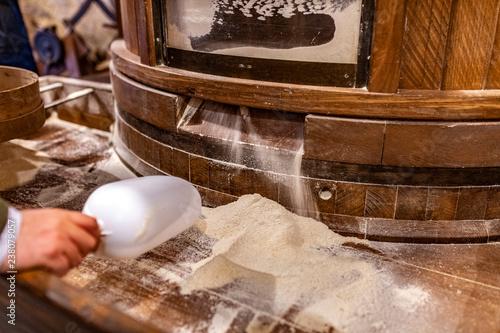 Farina che esce da una Mulino con macina in pietra e viene confezionata Wallpaper Mural