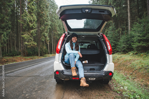 Obraz na plátne young adult woman sitting in suv trunk resting after road trip at road side in m