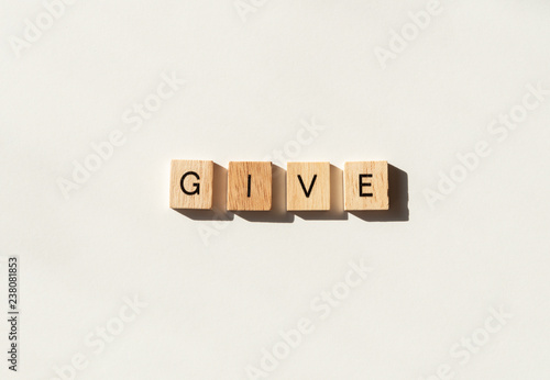 Photo The word GIVE spelled in wooden letter tiles flat lay on white.