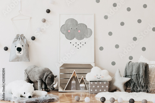 Stylish scandinavian newborn baby room with toys, teddy bears, cotton lamps and cloud. Modern interior with mock up photo frame. White background walls with dots pattern.