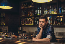 Young Bartender Leaning On Bar Counter Thoughtful