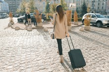 Young Beautiful Woman Walking Along City Street With Travel Suitcase And Cell Phone. Fashionable Brunette Girl, View From The Back, Copy Space