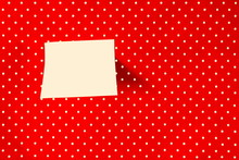 Sticky Note On Red Polka Dot Background. While Dots On Red Background.
